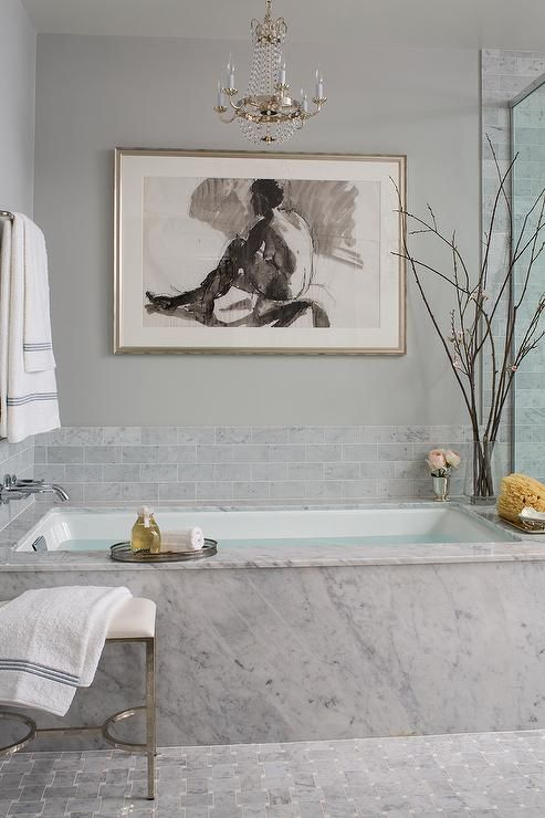 grey marble covers the bathtub and grey marble tiles for a backsplash create a chic unified look