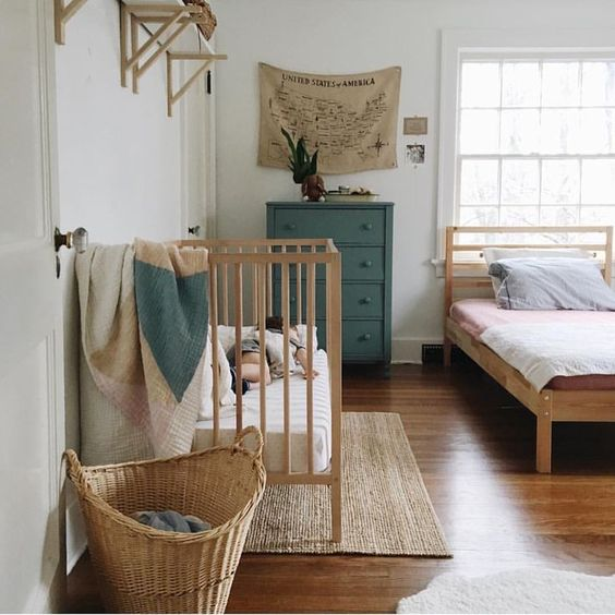 a natural master bedroom with a vintage feel and a baby's nook with a crib, a basket and shelves in the same style