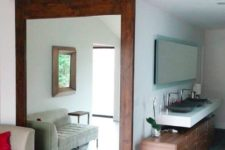 22 a rich-colored large barn door features a big mirror that doubles the living room space