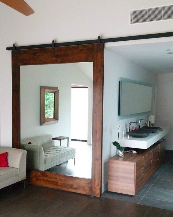 a rich-colored large barn door features a big mirror that doubles the living room space