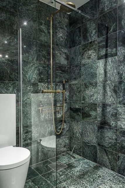 contemporary bathroom with brass fixtures and dark green marble tiles for a catchy modern look