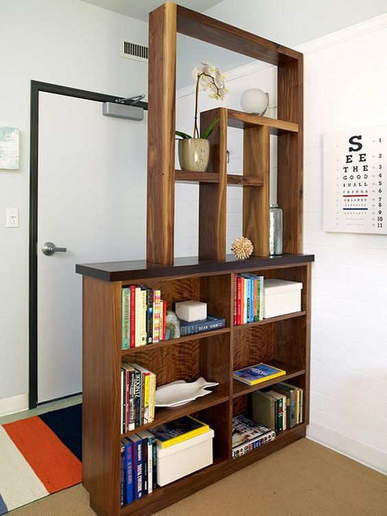 create an entryway if there's none with a large wooden shelving unit with several box shelves