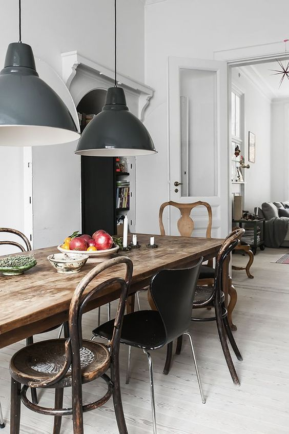 a rustic antique table and a mix of rustic and modern chairs of metal, wood and leather