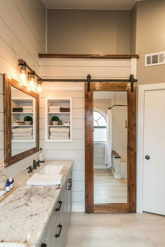 a sliding barn door with a mirror insert is a great idea for the bathroom as the mirror is a must for such a space