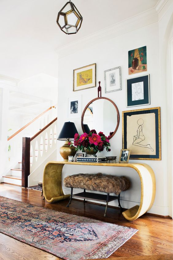 a stunning curved console, a fur ottoman and a gallery wall with various art and a mirror