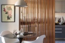 23 a vertical wooden plank screens gently separates the kitchen and the dining space
