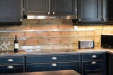 23 vintage black cabinets, silver handles and a wooden plank backsplash with an additional glass screen for protection