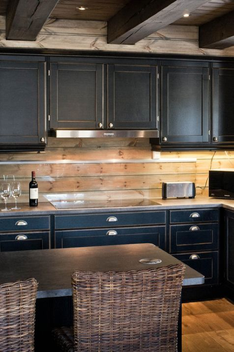 vintage black cabinets, silver handles and a wooden plank backsplash with an additional glass screen for protection