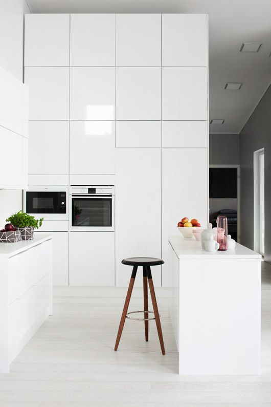 a high gloss white kitchen with tall wall cabinets and an island