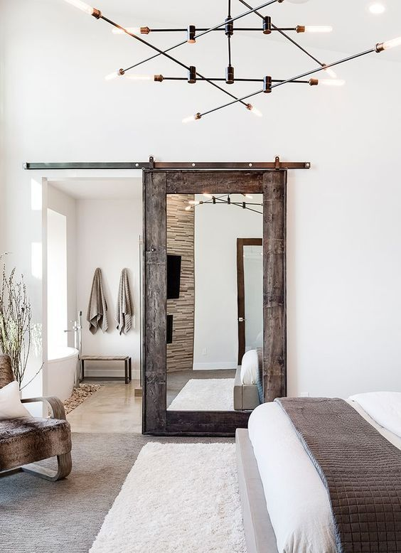 a sliding barn door with a mirror is a chic idea, a combo of modern and rustic things for a modern farmhouse