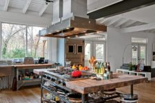 24 a vintage industrial kitchen island with metal pipe legs and a shelf and a wooden countertop