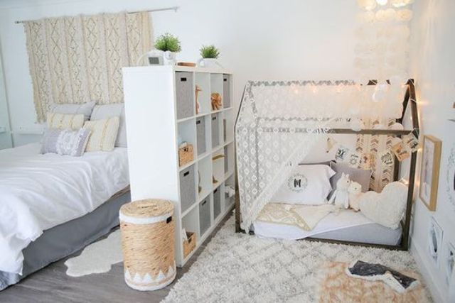 separate a nursery nook in your master bedroom with a comfy white shelving unit inserting some boxes for more privacy