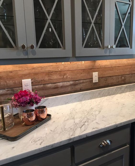 vintage grey cabinets, a marble countertop and a wooden plank backsplash for a less formal look
