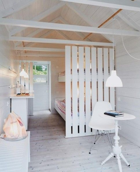 a white wooden plank screen gently separates a small shabby chic studio space