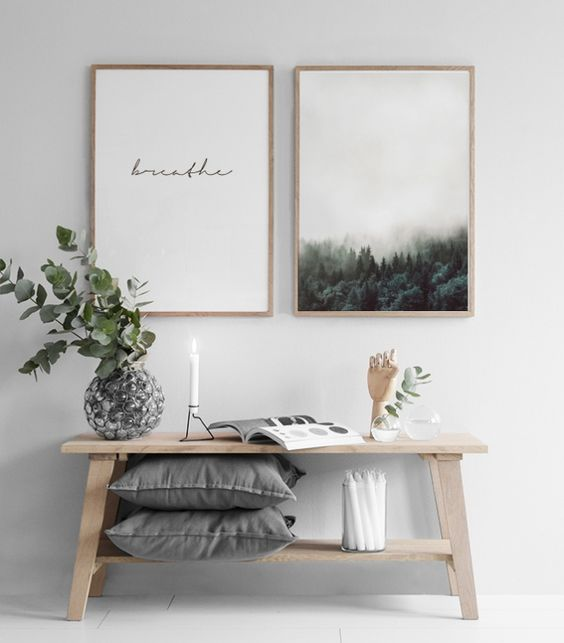 a wooden bench with a shelf for storage and a duo of artworks for a peaceful and calm look