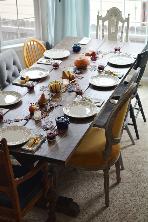 an antique rustic table with a mix of bold chairs in vintage, shabby chic and modern style in various colors