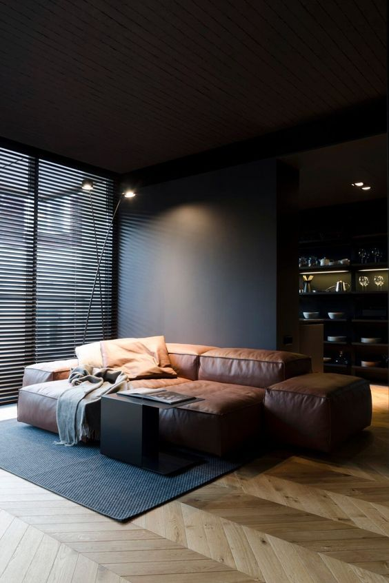 the living room is defined by a stylish brown leather sofa and black walls