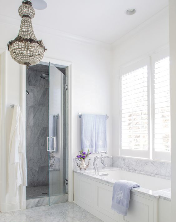 white and grey marble was used to clad the backsplash and the bathtub to add a refined feel