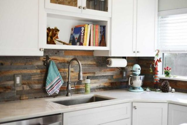 white cabinets are enlivened with a reclaimed wood kitchen backsplash that looks very rustic