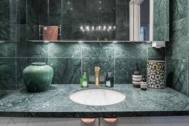 a green marble countertop and matching tiles that cover the walls for a stunning modern look