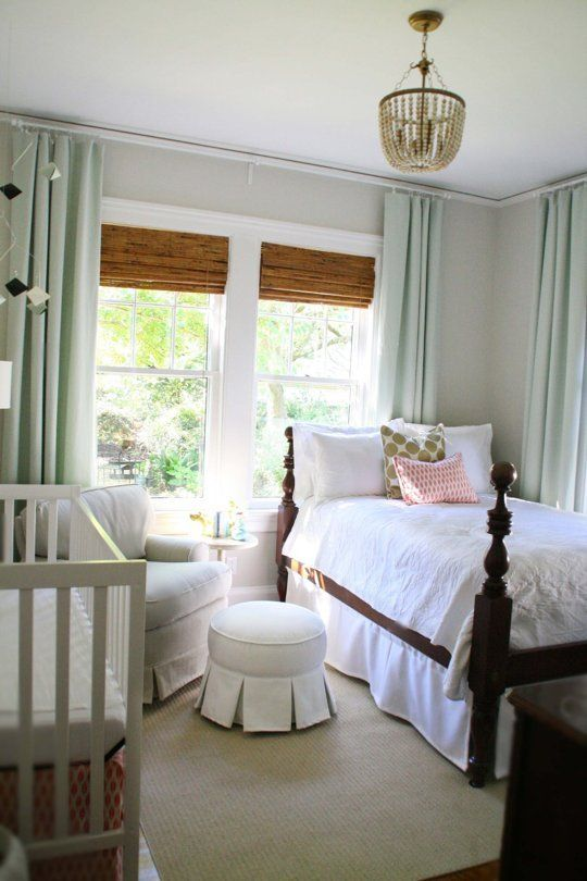 a traditional farmhouse bedroom with a crib by the wall and a comfy chair with an ottoman