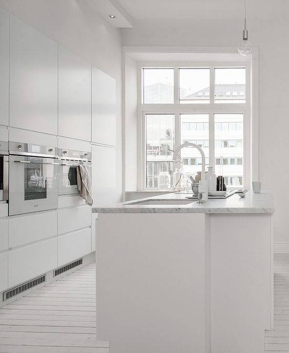 a whitewashed wooden floor and a white marble countertop are ideal to spruce up an all-white kitchen