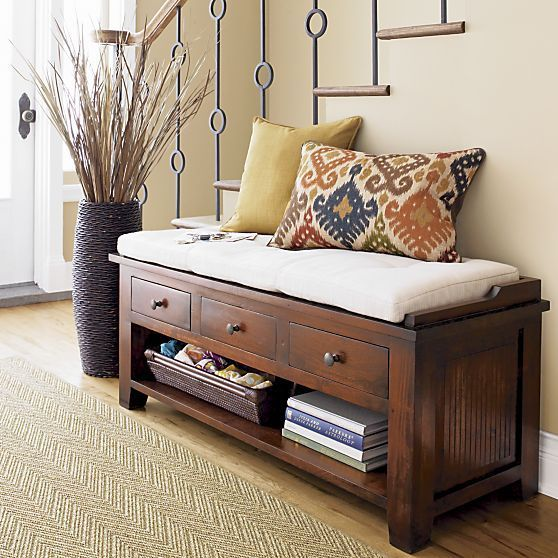 a wooden bench with a cushion, drawers and an open shelf for storage for a rustic space