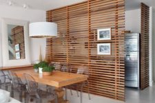 26 the dining space is made uncluttered with horizontal wooden plank screens that separate it from the kitchen