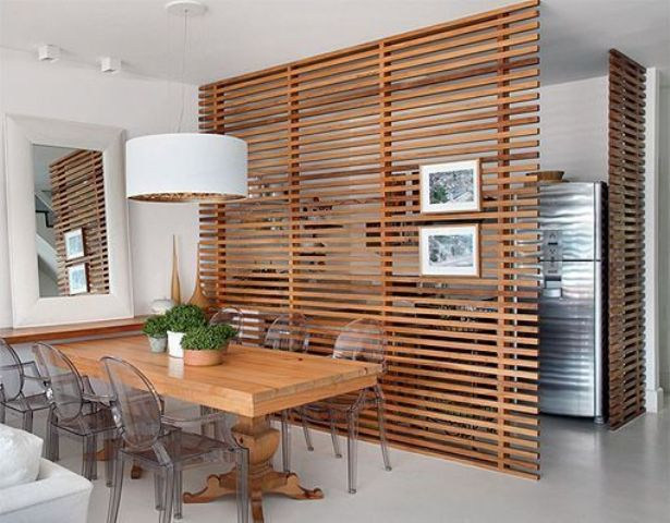 the dining space is made uncluttered with horizontal wooden plank screens that separate it from the kitchen