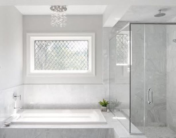 white marble tiles in the shower are extended to make a backsplash and cover the bathtub, too