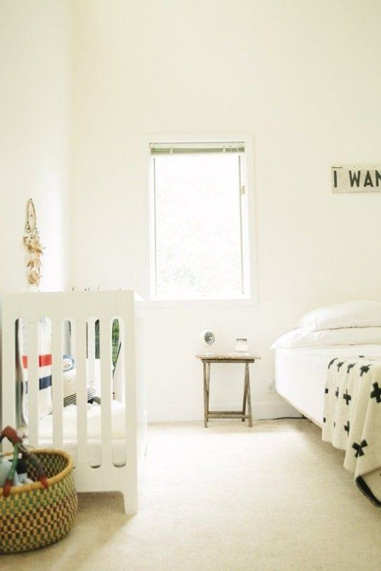 an uncluttered Scandinavian space with a crib, a basket and a bed with a small nightstand