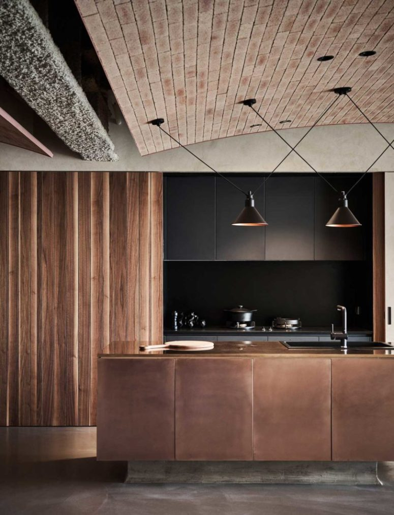 The kitchen is done with black sleek cabinets that can be hidden with wooden sliding doors and a copper clad kitchen island