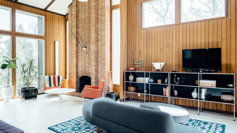 The living space is done with a brick clad fireplace and muted colored mid-century modern furniture