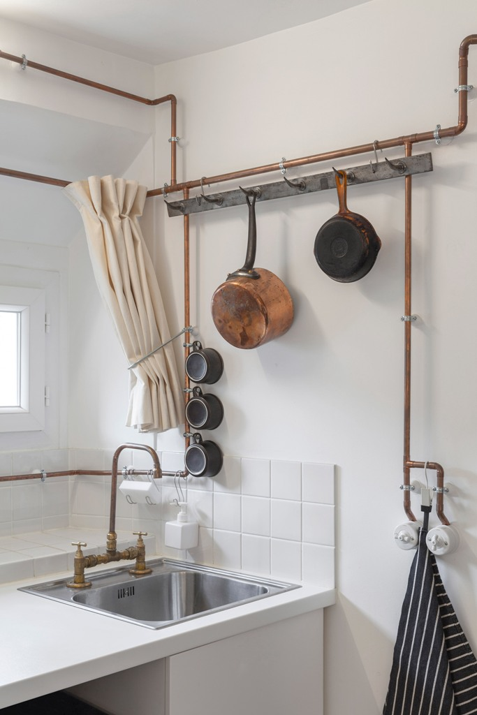 The whole apartment is done in white, and the main feature is copper pipes that are shown in the whole apartment and serve various purposes