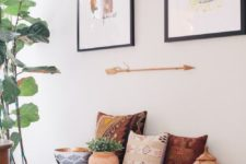 02 a black bench, colorful pillows, potted plants, artworks and an arrow