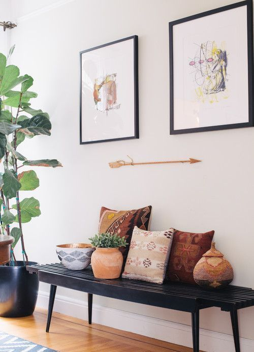 a black bench, colorful pillows, potted plants, artworks and an arrow