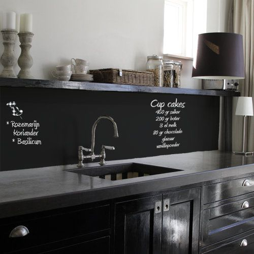 a black glossy kitchen with dark concrete countertops and a chalkboard backsplash to chalk on recipes and lists