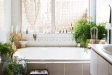 02 a boho chic bathroom with potted greenery, a creative chandelier, candle holders and a faux fur rug