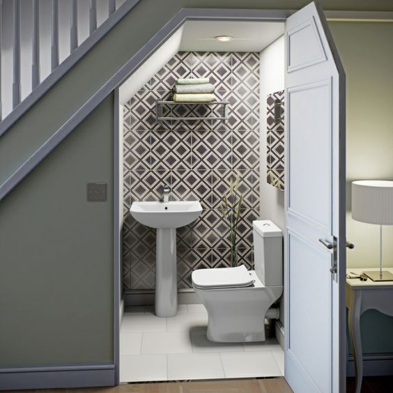 a contemporary powder room done with geometric tiles, a wall-mounted shelf for storage