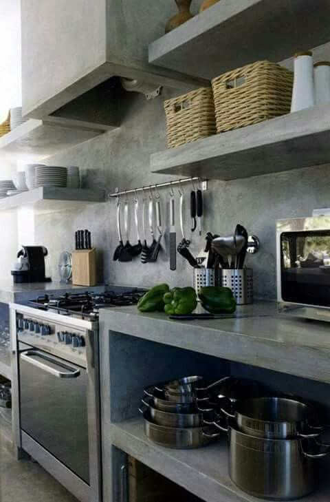 a fully industrial kitchen done in grey concrete, with a backsplash and countertops