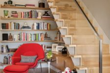 02 a reading nook with wall-mounted shelves, cabinets and a bold red mid-century modern chair