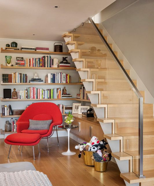 a reading nook with wall-mounted shelves, cabinets and a bold red mid-century modern chair