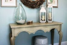 02 a vintage carved console, lanterns with star fish, a bottle with sand, a wood clad mirror