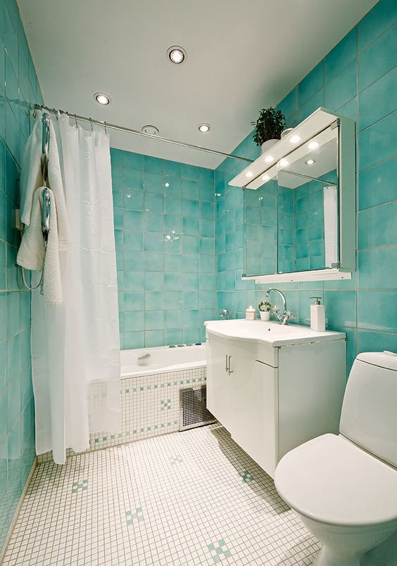 turquoise watercolor tiles cover the whole space and look nice with litte white ones on the floor