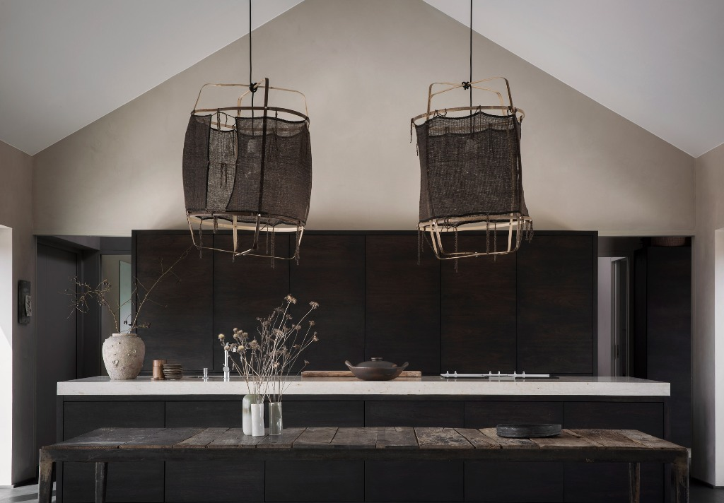 The kitchen is dark, with almost black timber cabinets and a kitchen island, a weathered wood bench and pendant lamps with dark lampshades