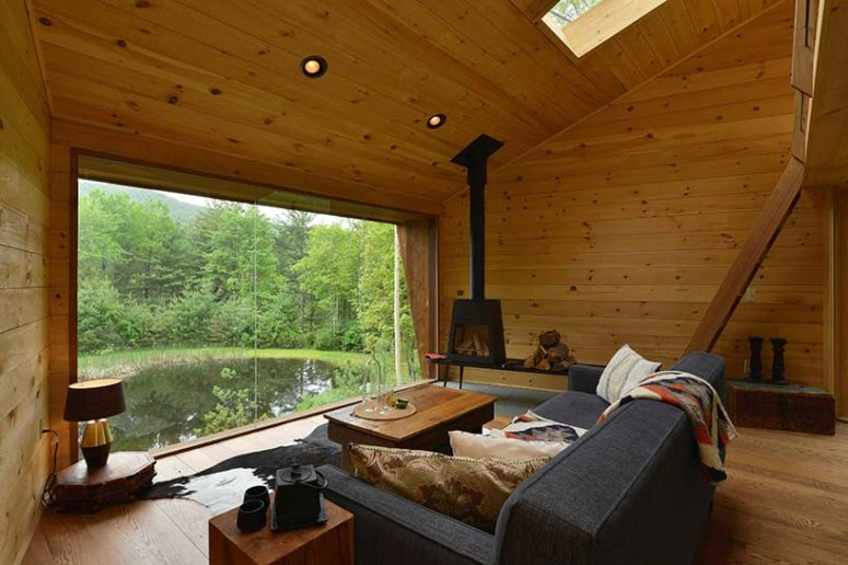 The living space features a grey sofa, some wooden side tables and a metal hearth, a glazed wall features an amazing view