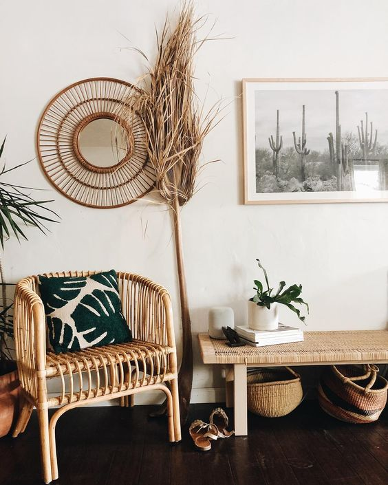 a boho desert entryway with rattan furniture, cacti artworks, potted plants and grasses