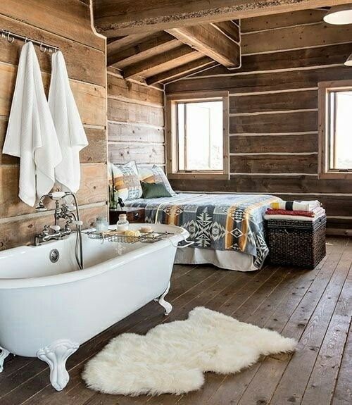 a chalet bedroom fully clad with wood with a vintage clawfoot tub that adds interest to the space