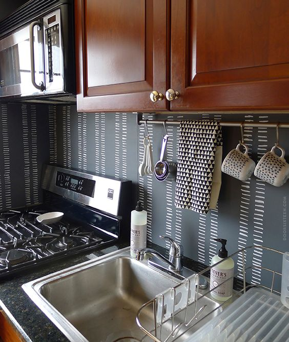 a chalkboard backsplash and rich-colored wooden cabinets create a bold contrast