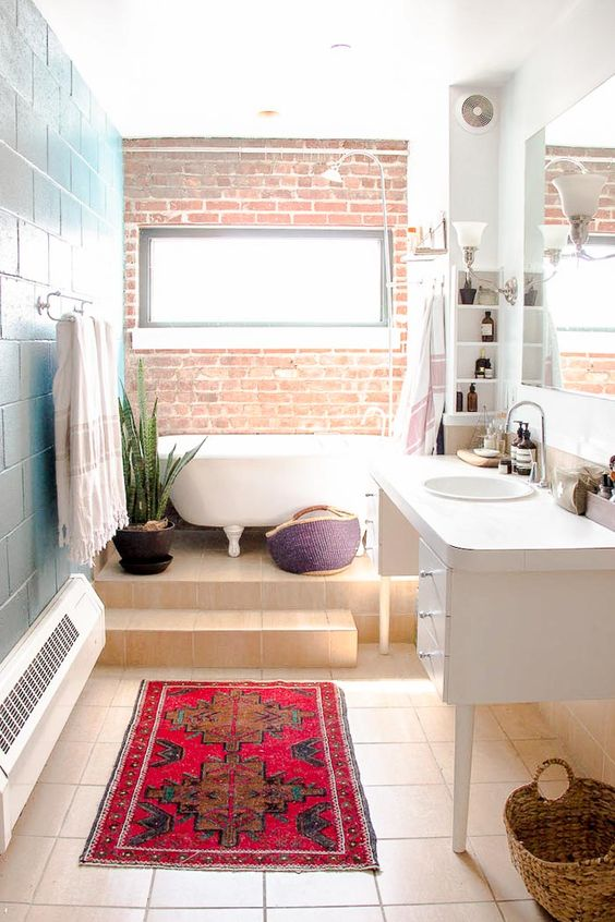 a colorful industrial and boho chic space with a brick wall, baskets and potted succulents